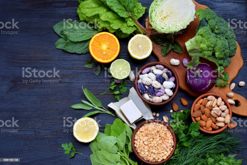 Composition on a dark background of products containing folic acid, vitamin B9 - green leafy vegetables, citrus, beans, peas, nuts, yeast. Top view. Flat lay stock photo