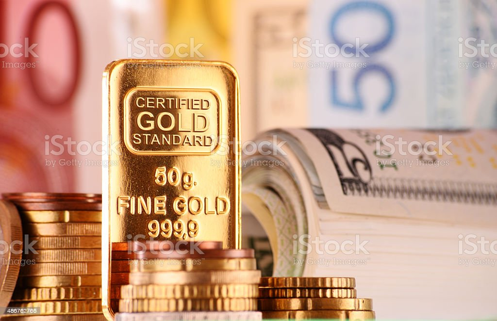 Composition with 50 gram gold bar, banknotes and coins stock photo
