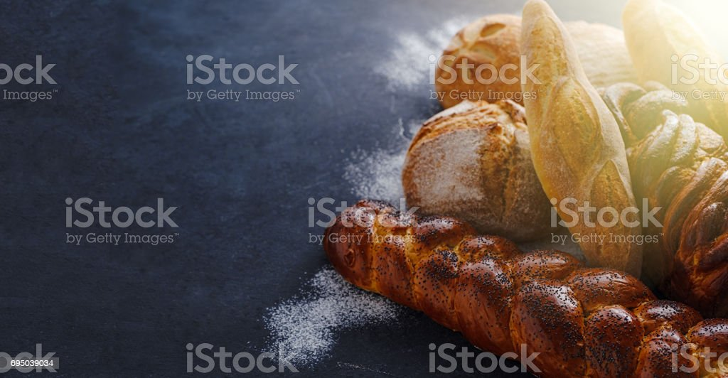 Composition with fresh bread over dark background. stock photo