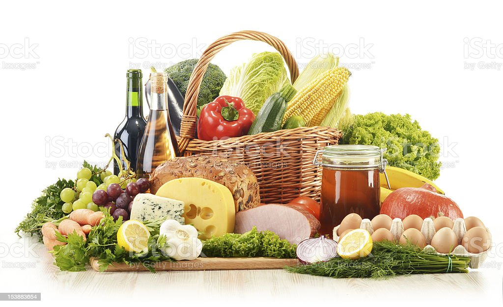 Composition with groceries in wicker basket on kitchen table royalty-free stock photo