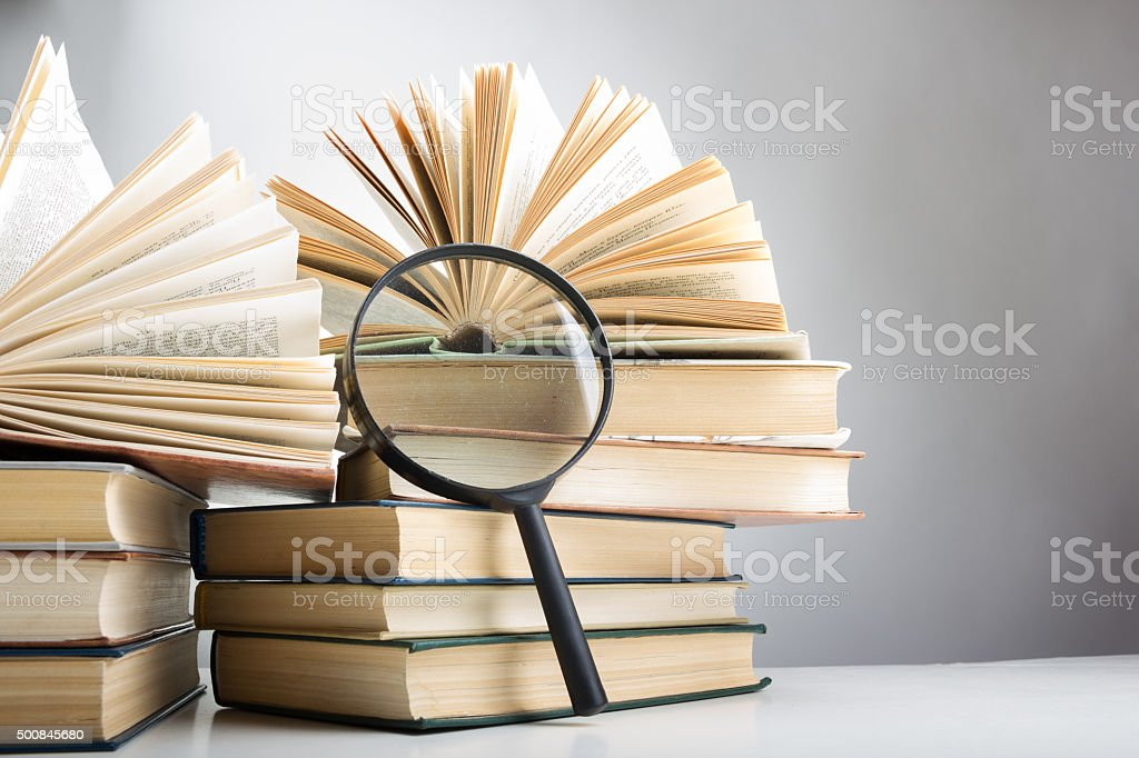 Composition with hardback books and magnifying glass..Education background. stock photo