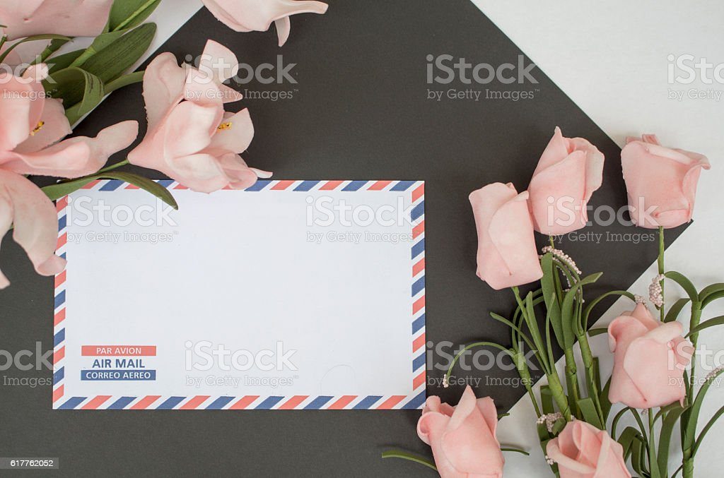 Composition with letter and flowers on white background stock photo