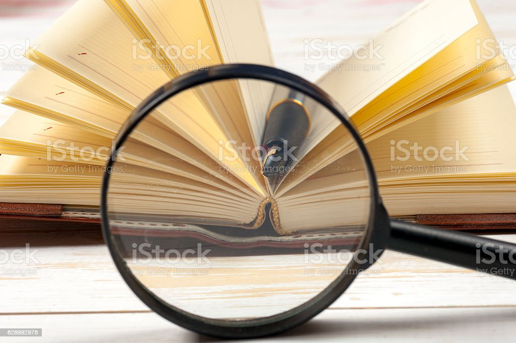 composition with open book and magnifying glass. stock photo