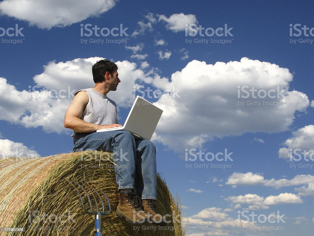 Compute Anywhere Photo: Man with Laptop Computer Sitting on Haystack royalty-free stock photo
