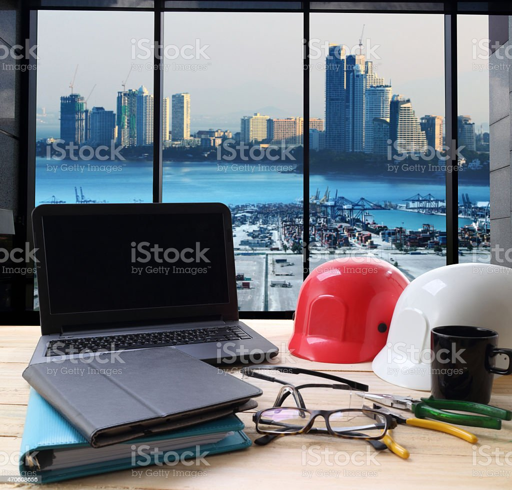 computer and builder's work tool on wooden table stock photo