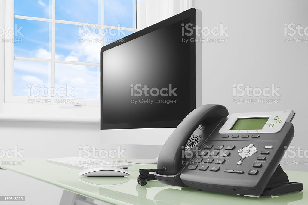 Computer and telephone on glass desk beside window royalty-free stock photo