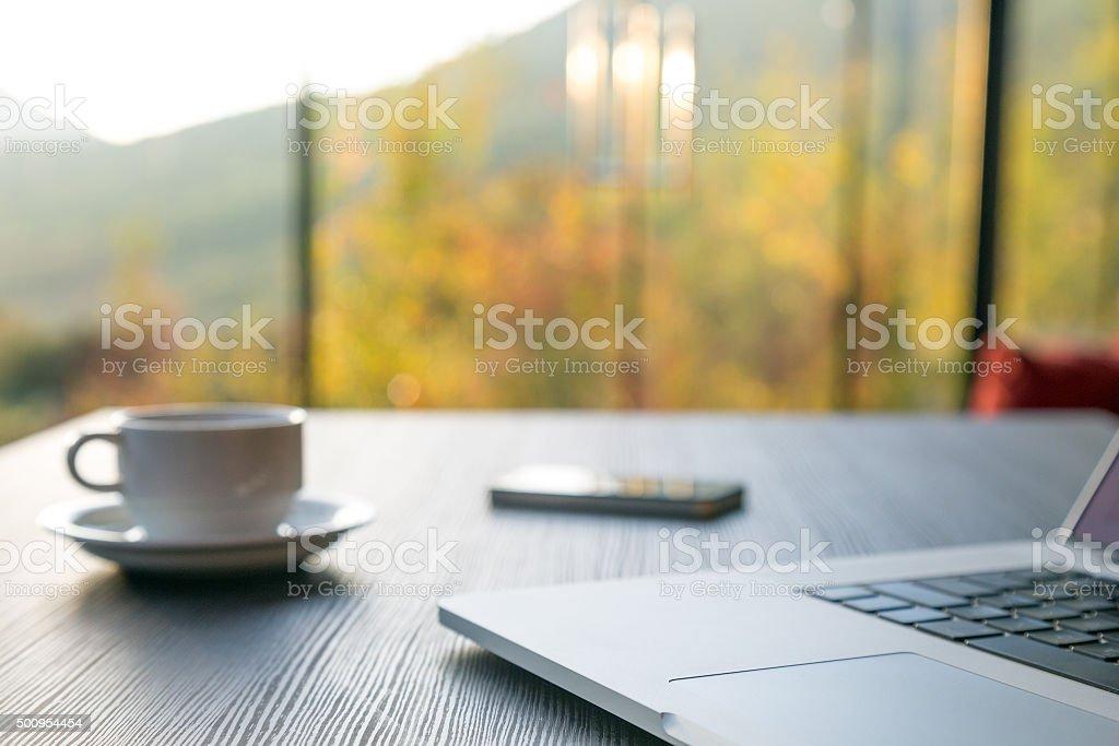 Computer Coffee Mug and Telephone on black wood table window stock photo