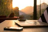Computer Coffee Mug Telephone on black wood table sun rising