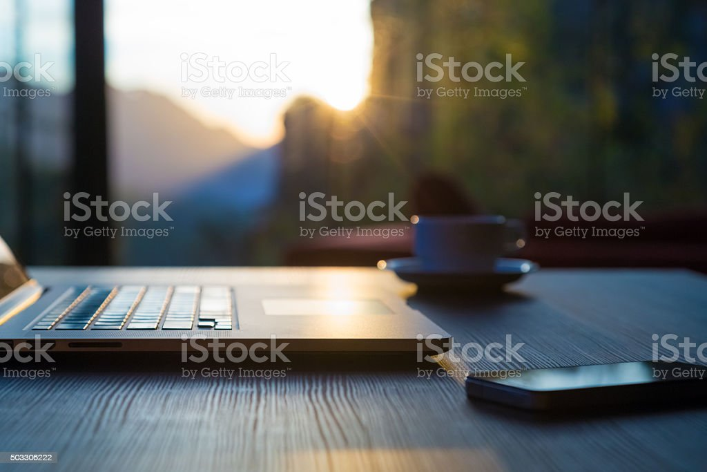 Computer Coffee Mug Telephone on black wood table sun rising stock photo