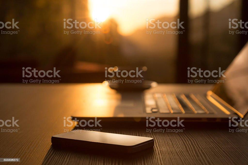 Computer Coffee Mug Telephone on black wood table sun rising stock photo