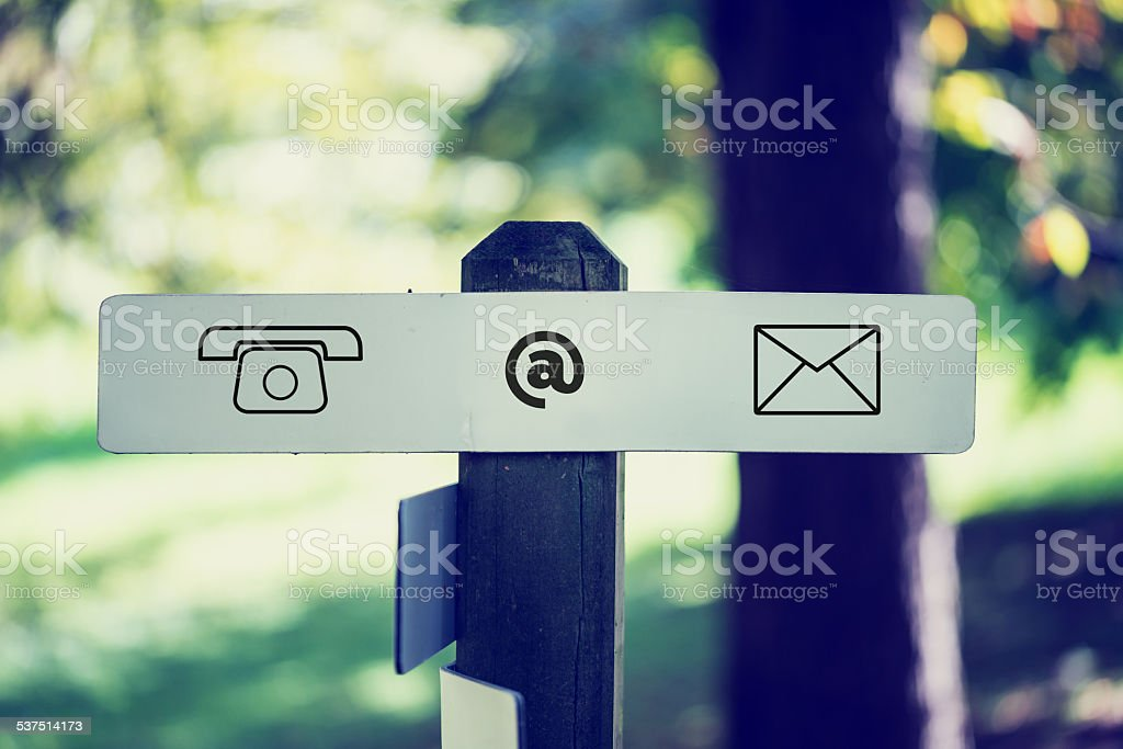Computer Contact Icons Sign on Outdoor Signpost stock photo