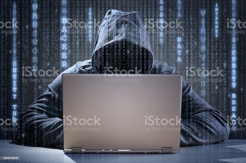 Computer hacker stealing data from a laptop stock photo