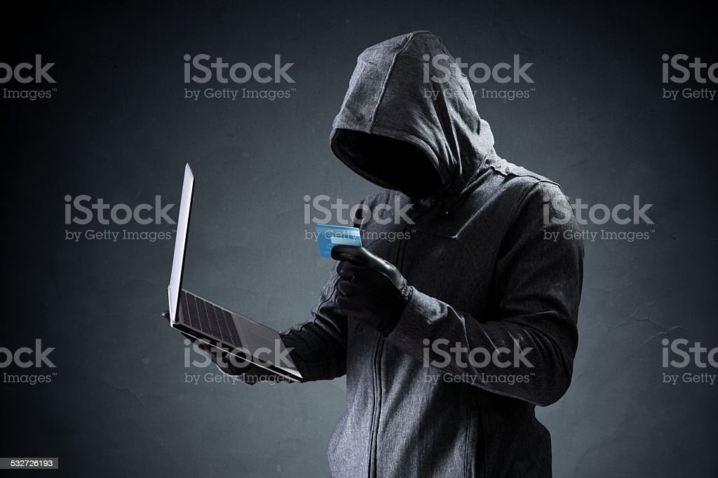 Computer hacker with credit card stealing data from a laptop stock photo