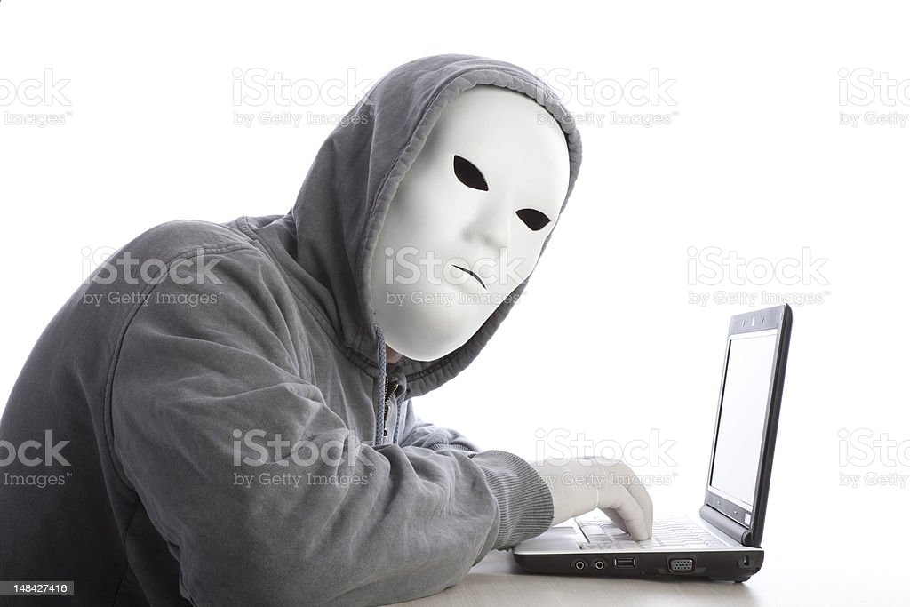Computer Hacker With Mask And Hood Using Laptop On White royalty-free stock photo