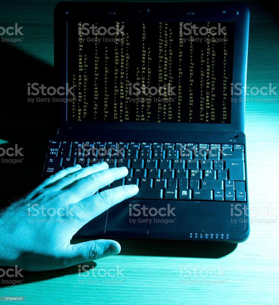 Computer hacker works on a laptop with green code royalty-free stock photo