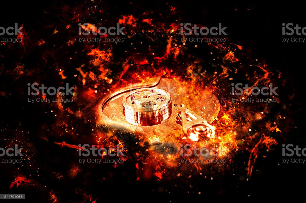 Computer hard disk on fire, burning in flames. stock photo