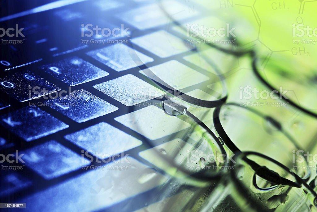 Computer keyboard and laboratory glass. stock photo