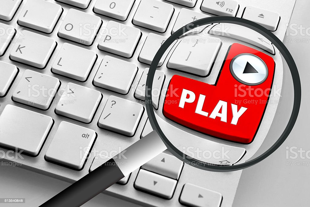 Computer keyboard with red play button and magnifying glass stock photo