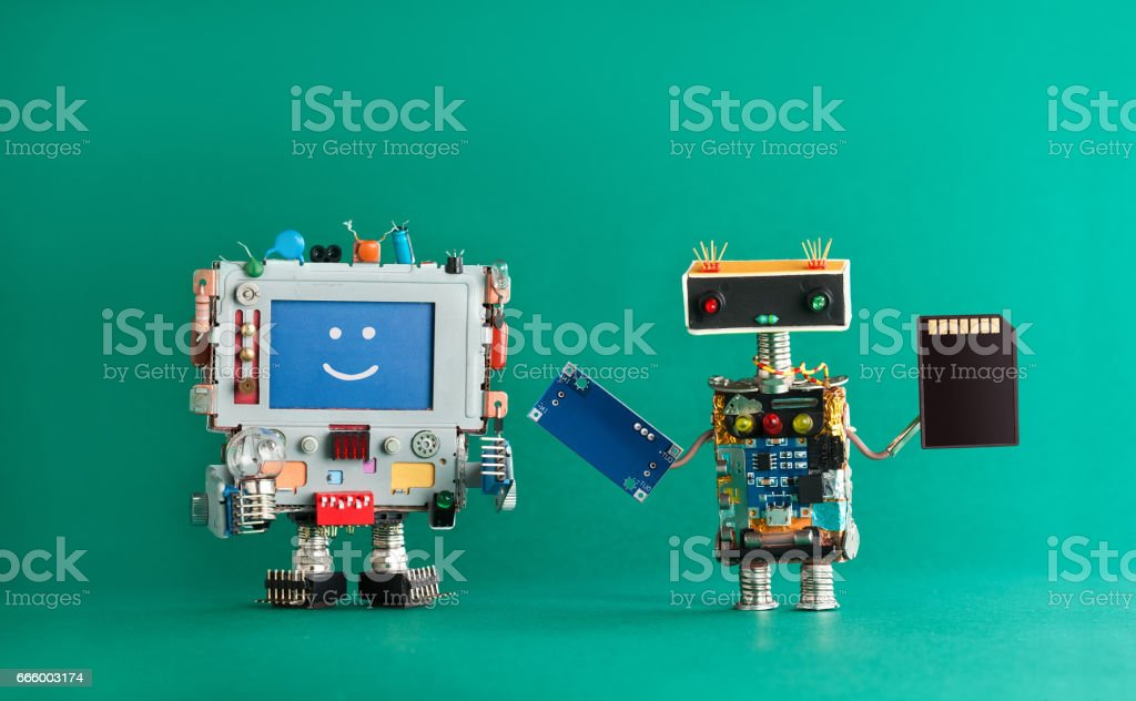 Computer repair renovation concept. Smiling monitor machine, robot serviceman with chip circuit storage memory card device. green background stock photo