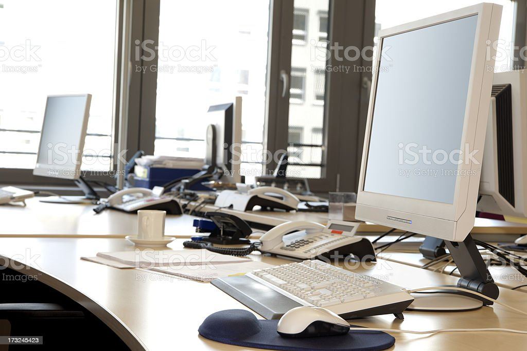 Computer Screens, Keypads, Telephones On Desktops In Office Interior stock photo