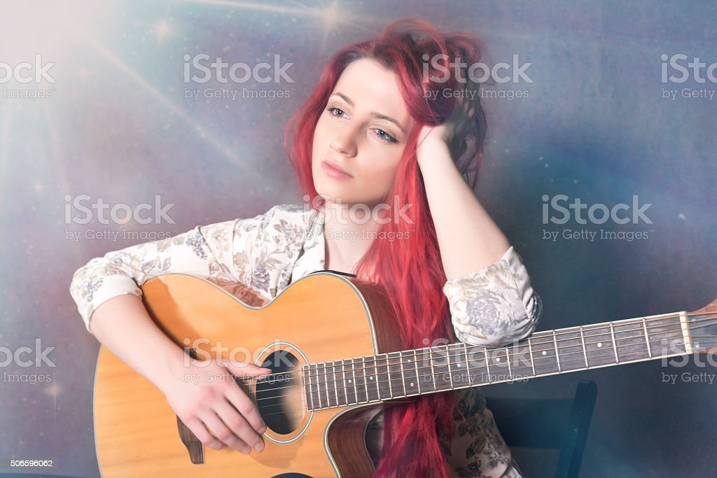 Conceived red haired girl with a guitar stock photo