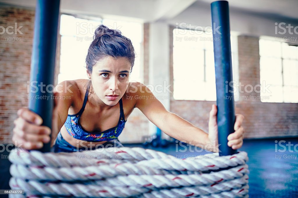 Concentrated athlete pushing battling rope sled in gym stock photo