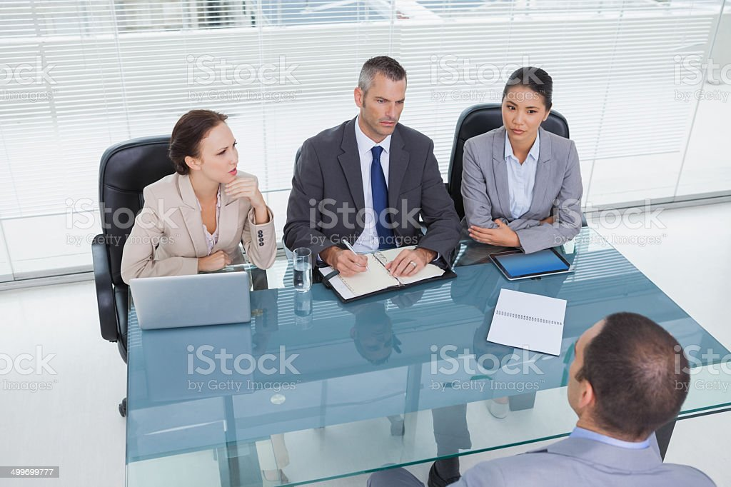 Concentrated business team interviewing experienced man royalty-free stock photo