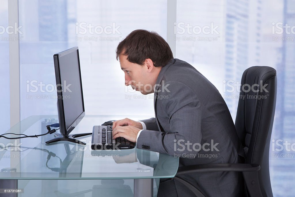 Concentrated Businessman Working On Computer In Office stock photo