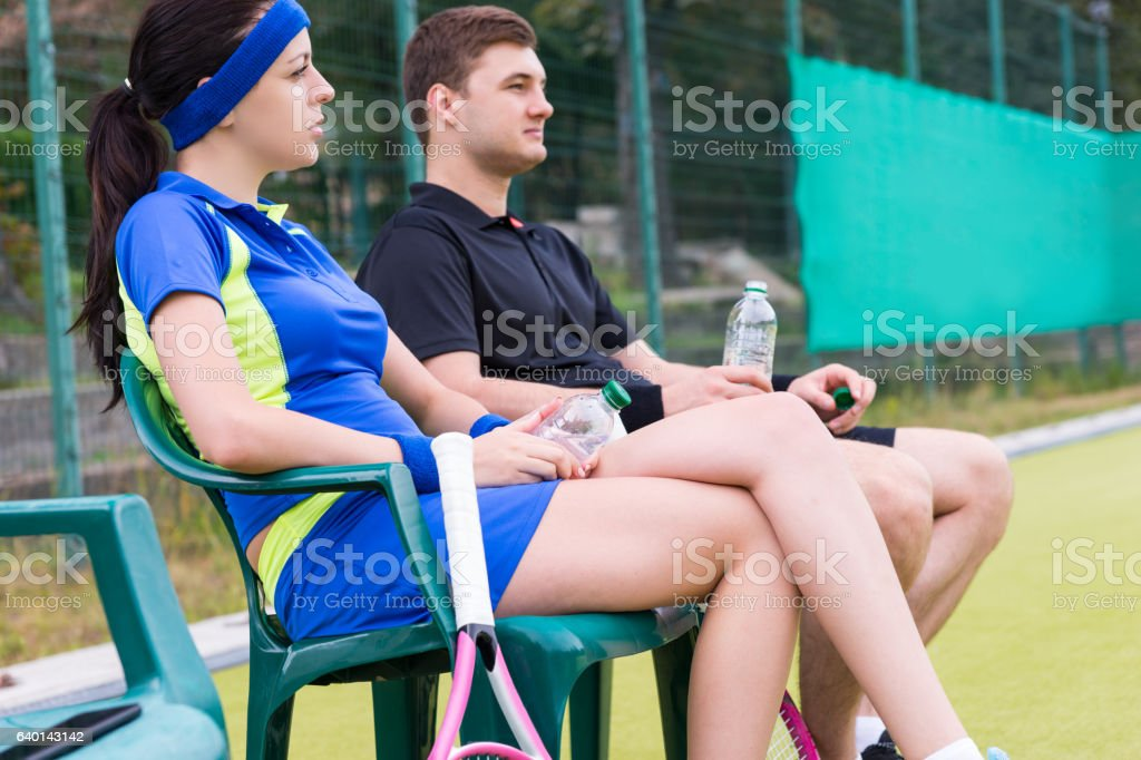 Concentrated couple of tennis players having a rest with bottle stock photo