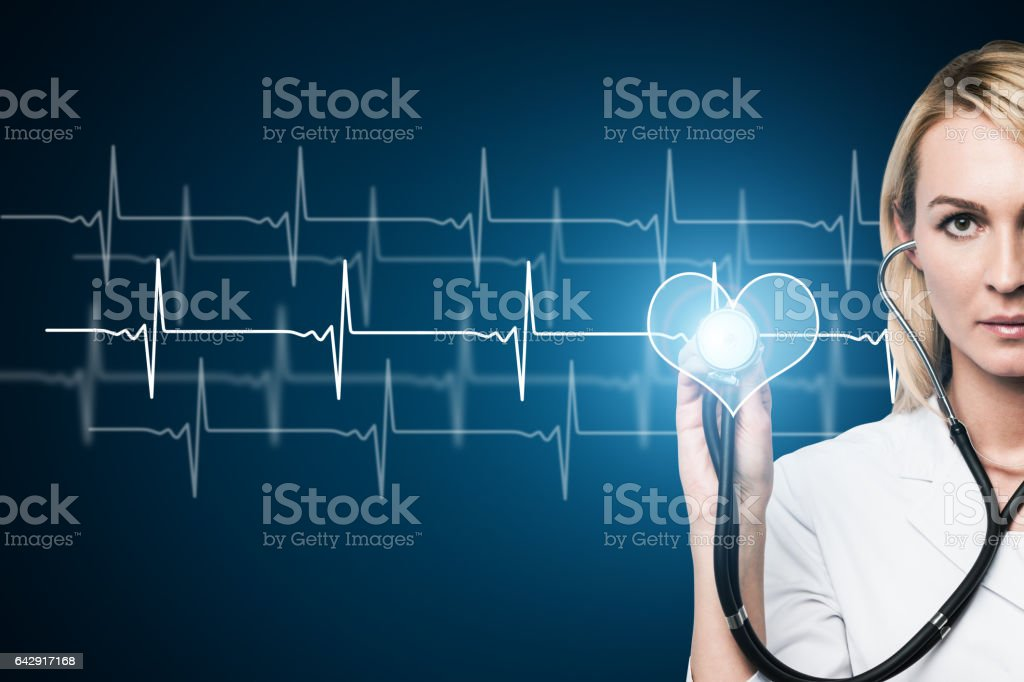 Concentrated doctor checking heartbeat stock photo