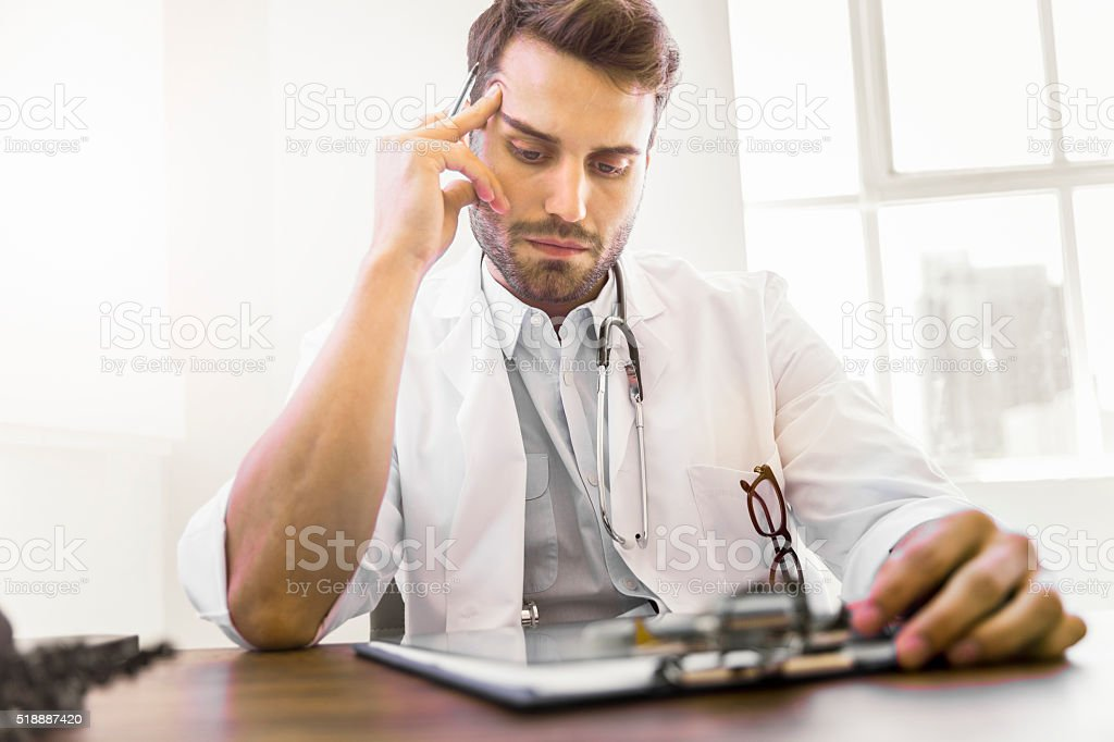 Concentrated doctor reading document on clipboard stock photo