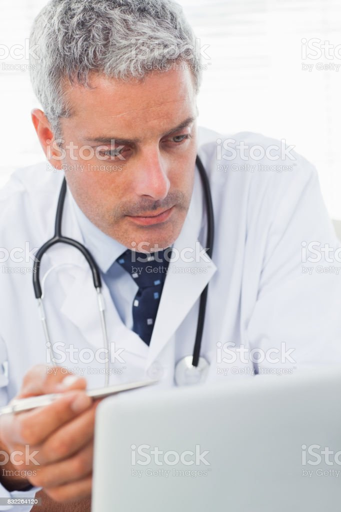 Concentrated doctor watching something on his laptop stock photo