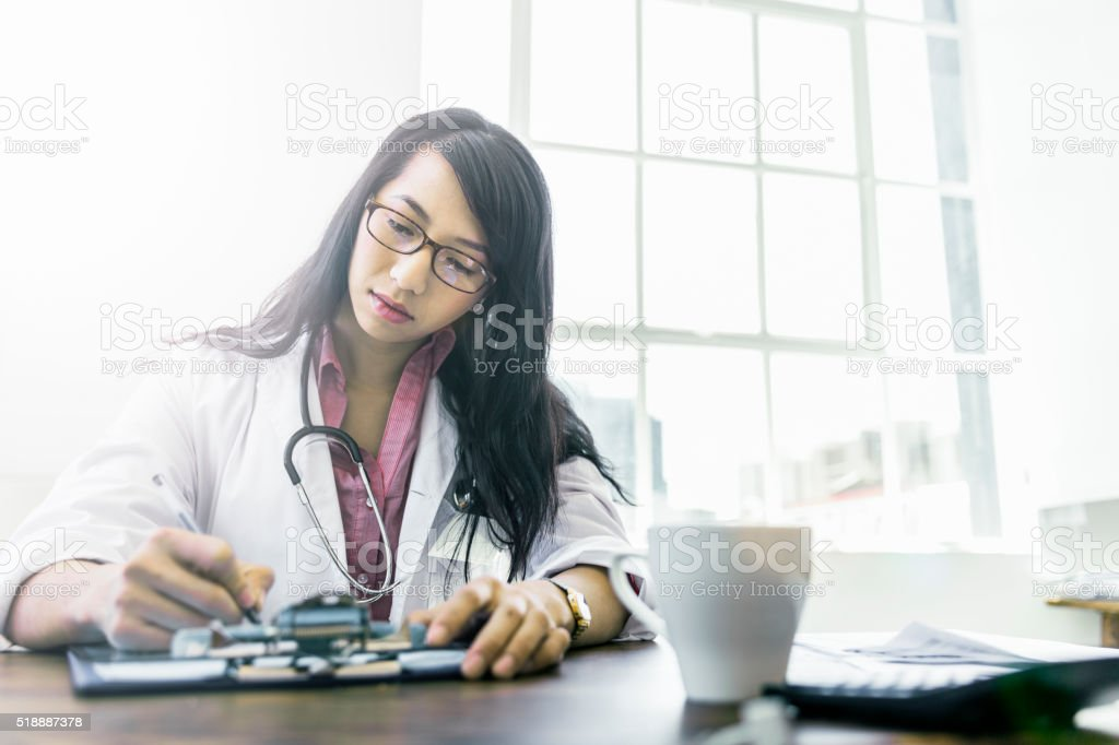 Concentrated doctor working at desk in clinic stock photo