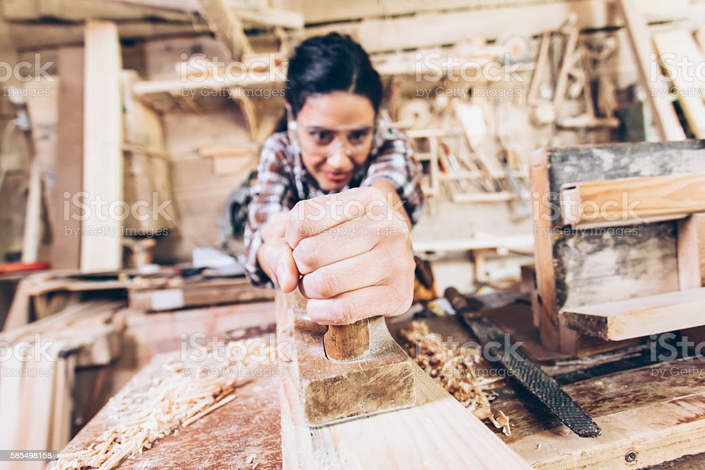 Concentrated female carpenter using grater at workshop stock photo
