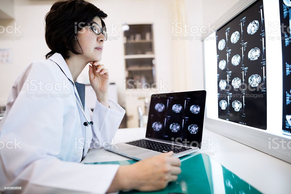 Concentrated female doctor examining MRIs in hospital stock photo