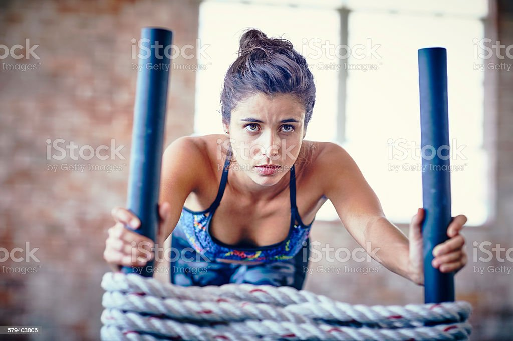 Concentrated female pushing rope sled in health club stock photo