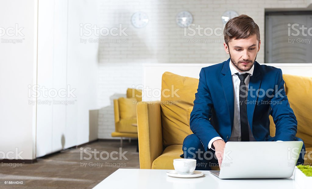 Concentrated handsoem businessman sitting on the couch stock photo