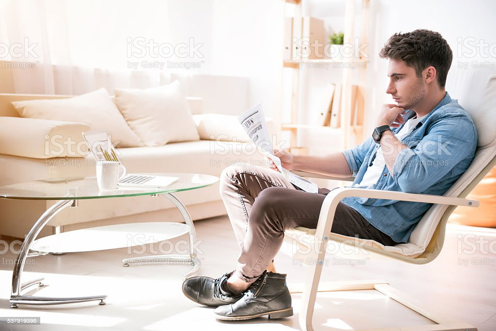 Concentrated handsome man reading newspaper stock photo