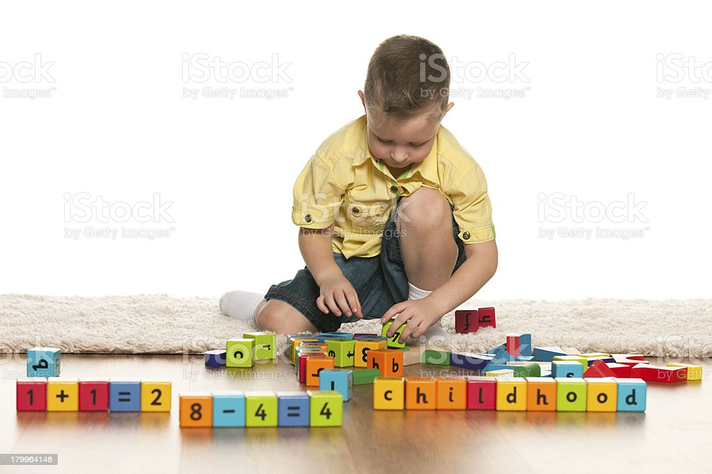 Concentrated little boy with toys on the floor royalty-free stock photo