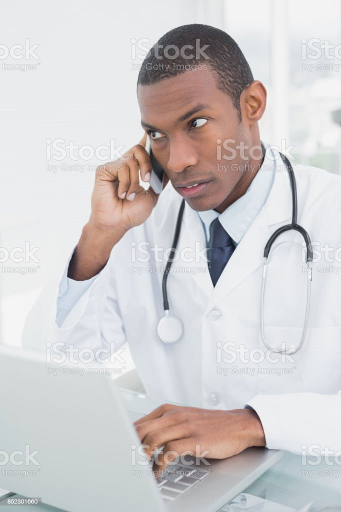 Concentrated male doctor using cellphone and laptop stock photo