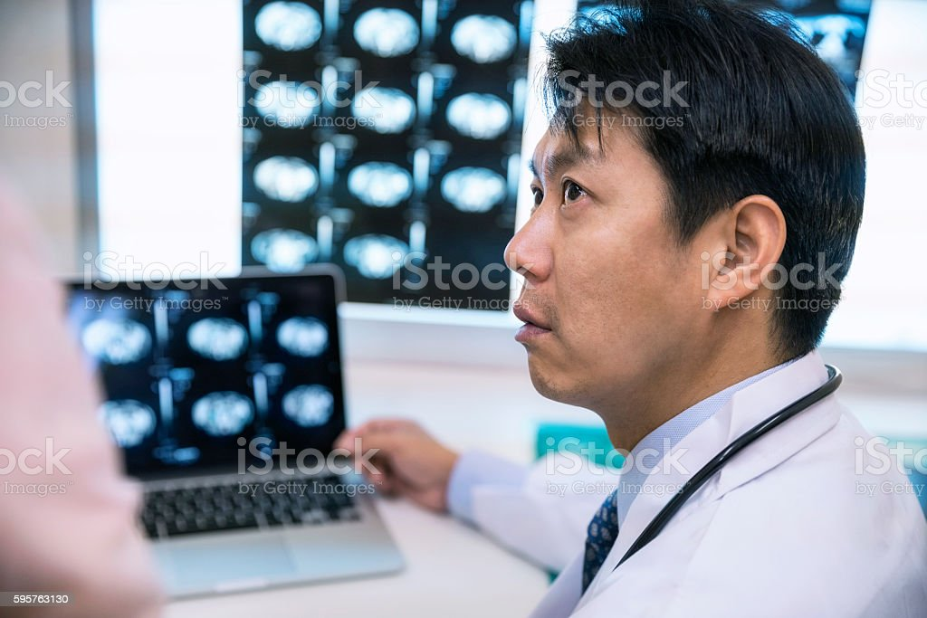 Concentrated male doctor with patient examining MRIs in hospital stock photo