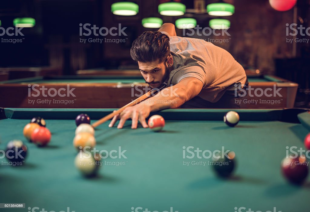 Concentrated man aiming at pool ball while playing snooker. stock photo
