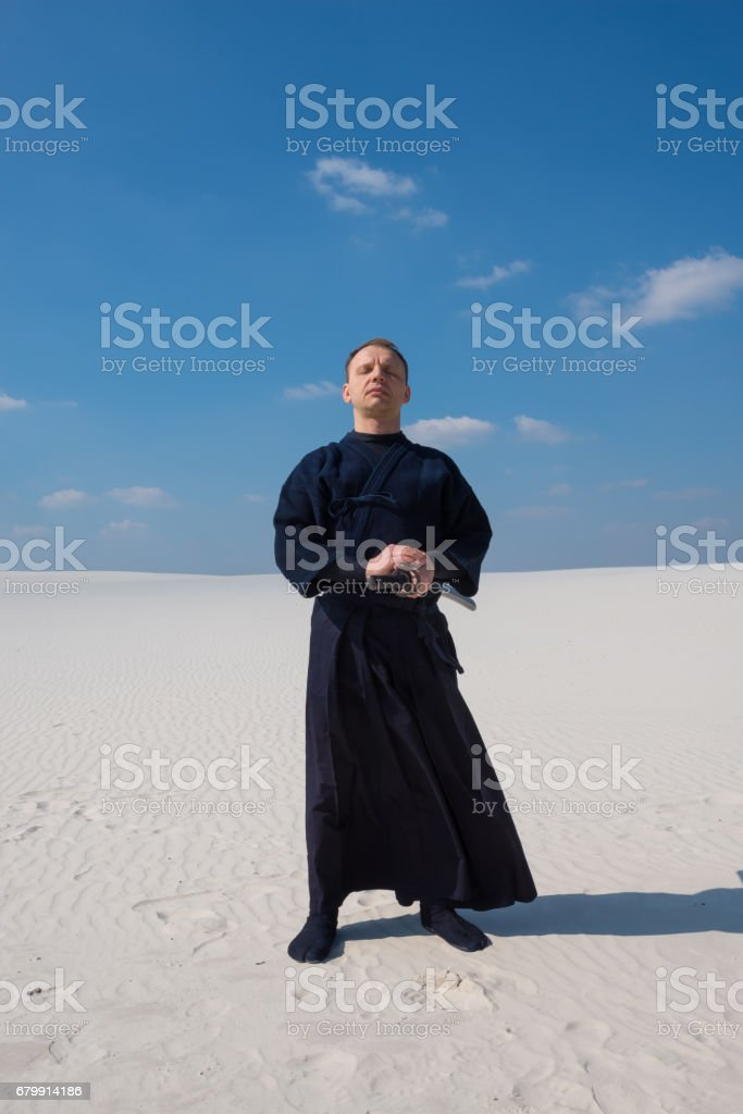 Concentrated man in traditional Japanese clothes stands and meditates stock photo