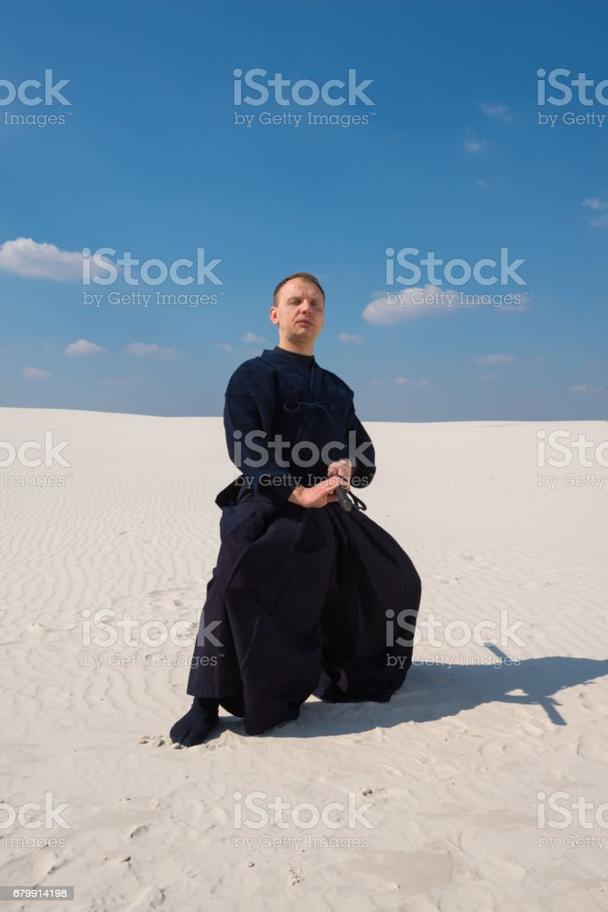 Concentrated man in traditional Japanese clothes took the position stock photo