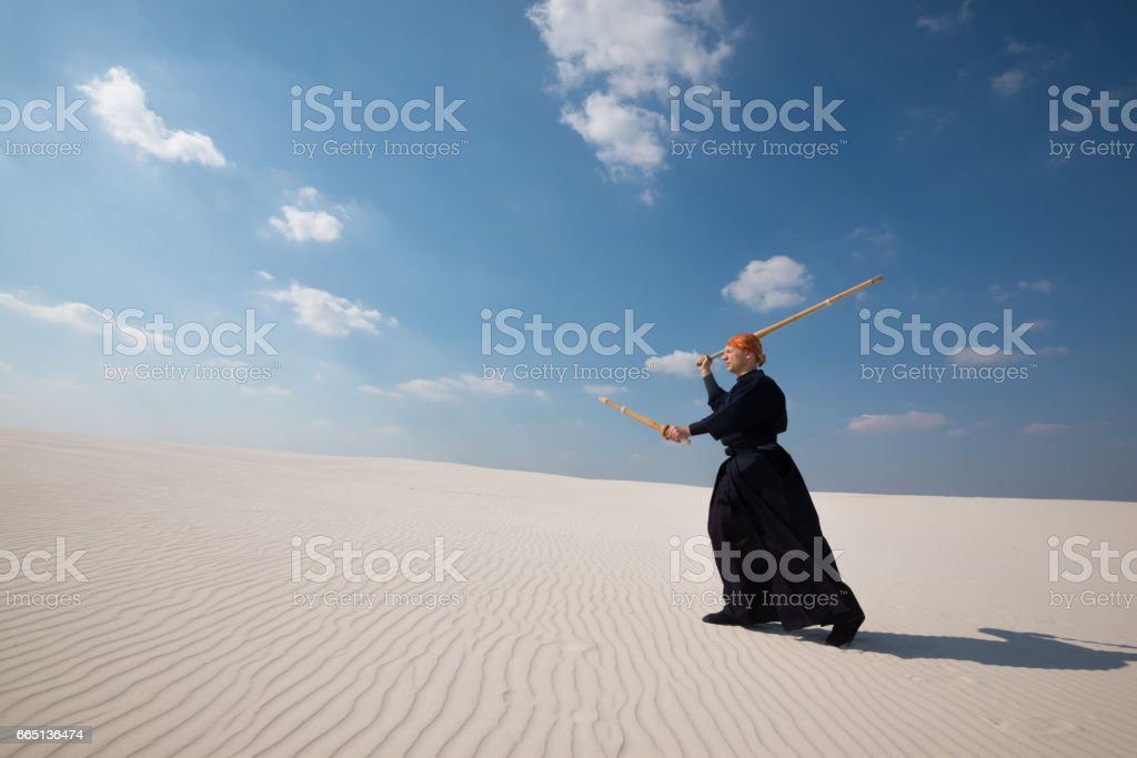 Concentrated man is practicing martial arts in a desert stock photo