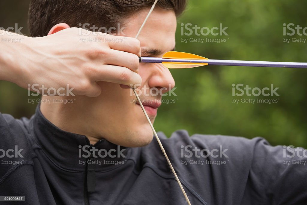 Concentrated man practicing archery stock photo