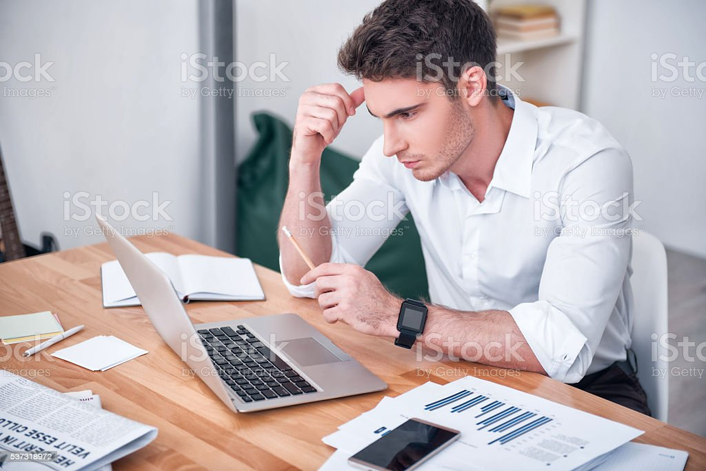 Concentrated man sitting at the table stock photo