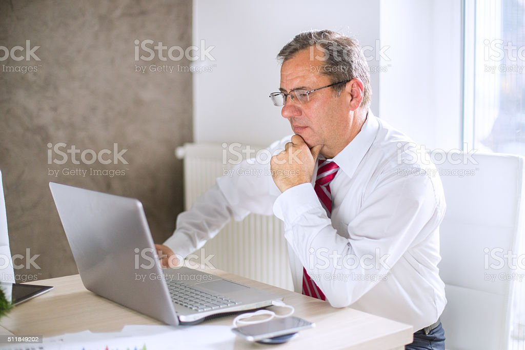 Concentrated mature businessman stock photo