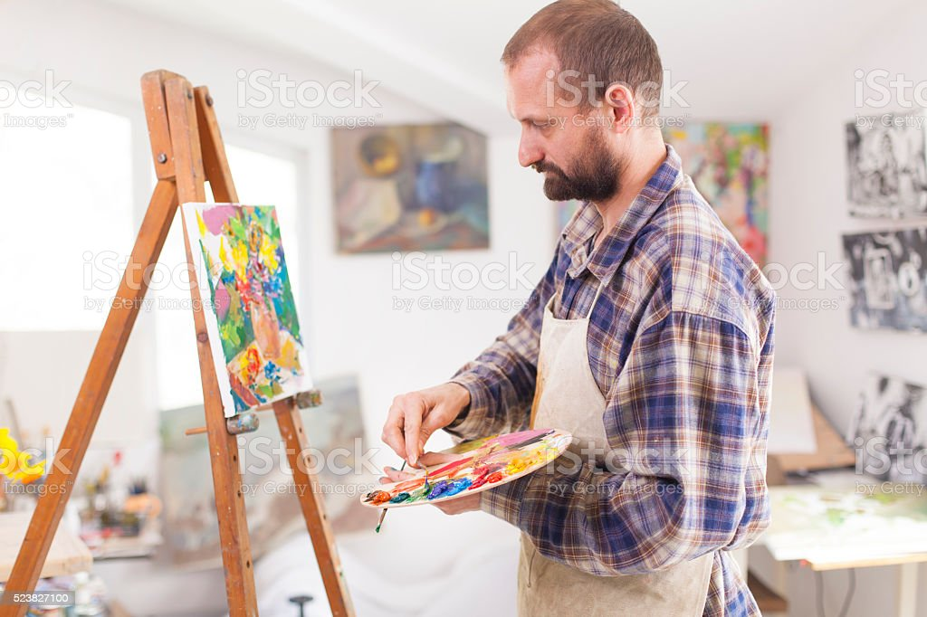 Concentrated painter working at his studio-side view stock photo