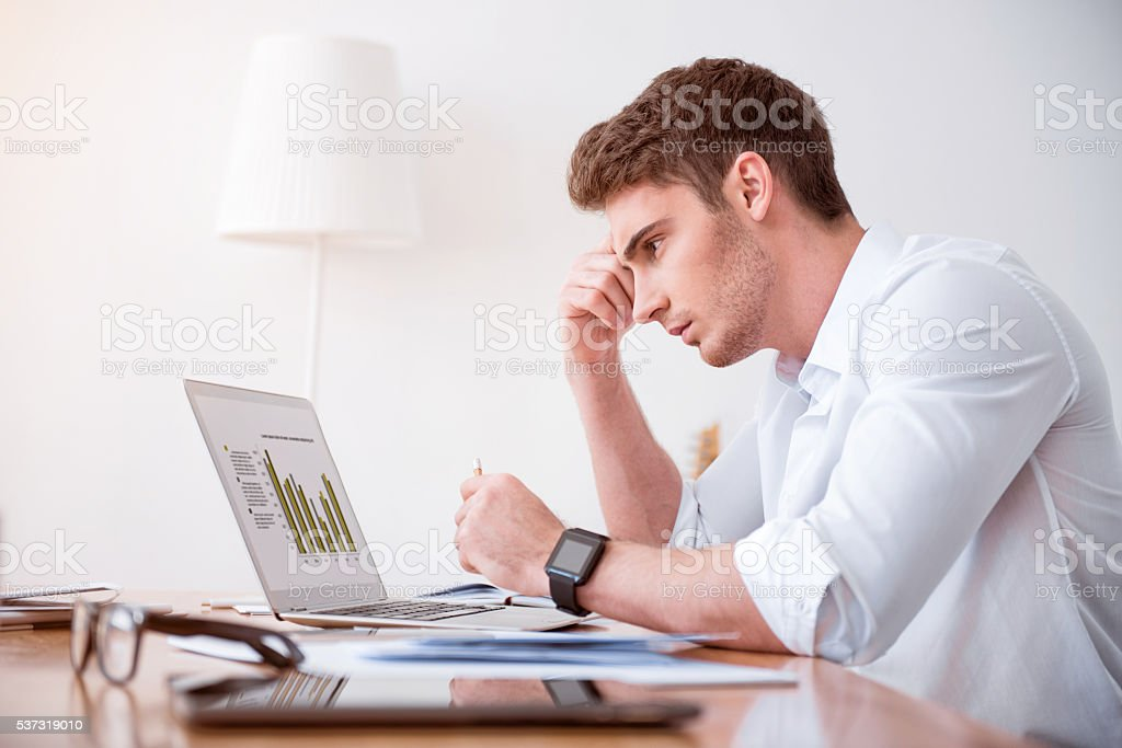 Concentrated  serious man sitting at the table stock photo
